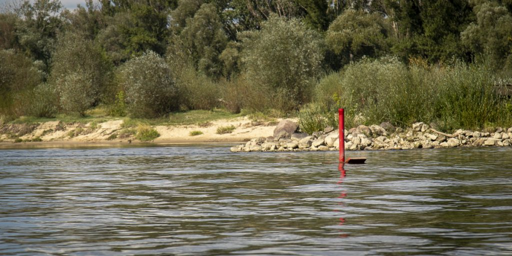 Right side of a fairway is marked by a red barrel or a column topped with a cylinder. When going downstream pass it on your right side, while going upstream pass it on your left side.