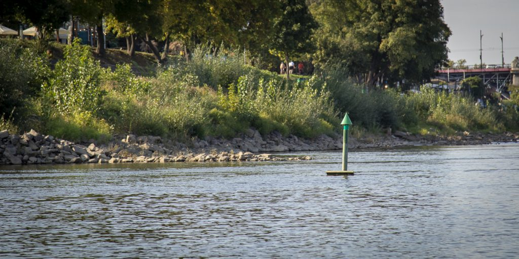 Left side of a fairway is marked by green signs such as a green cone or green column topped with a cone.  When going downstream pass it on your left side, while going upstream pass it on your right side.